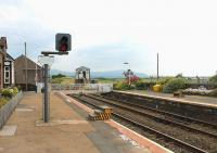 Looking south towards Ravenglass at Drigg station in July 2013. The mechanical signalbox controls colour light signals that protect the level crossing and form a block section between Sellafield and Bootle boxes. Note the steps on both low platforms to allow easier access to the trains. Presumably these will in due course be replaced by the new <I>Harrington Humps</I> as at Seascale, the next station north of here. <br><br>[Mark Bartlett&nbsp;27/07/2013]