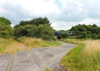 Looking north east along the trackbed of the Eskmeals gun range branch towards the junction with the Cumbrian Coast line as a Carlisle to Barrow service passes on 27 July 2013. The Vickers Gun Range Sidings box that controlled the branch access closed in 1983. It had an unusual Ransomes and Rapier <I>horse rake</I> 11-lever frame that is now preserved at the NRM York. [See image 44051] for a view in the opposite direction. Level crossings map reference SD088925<br><br>[Mark Bartlett&nbsp;27/07/2013]