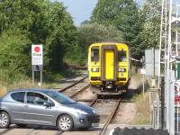 The driver of 153323 reaches out from his cab to operate the crossing barriers in order to enter Llandovery station with the 16.37 <I>Heart of Wales</I> line service forward to Swansea<br><br>[David Pesterfield&nbsp;01/08/2013]