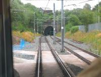 Metrolink tram driver's view of the site of Oldham Werneth station (closed 2009) from a Rochdale bound service. The tracks to Oldham Mumps through the tunnels were only temporarily electrified, as a town centre street running section was opened from the point in the foreground allowing the old railway line to close completely. [See image 21182] for the same location in 2008. <br><br>[Mark Bartlett&nbsp;31/07/2013]