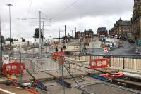 Metrolink street works in Oldham as seen from a passing Rochdale to East Didsbury tram. Completed in January 2014, trams now turn right at this point to pass through the town centre to rejoin the railway line formation at Werneth. The new Mumps tram stop is seen being built near the buildings at the top of the hill. [See image 44095] for a  view of this location in the opposite direction. <br><br>[Mark Bartlett&nbsp;31/07/2013]