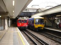 Hammersmith and City line unit 5553 runs into the west bound H&C platform at Paddington station on 9 August, passing First Great Western Turbo DMU 165129 stabled at main line platform 14. <br><br>[David Pesterfield&nbsp;09/08/2013]