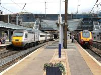 Changing face of Haymarket - scene on 9 August 2013 looking east. On the left is the East Coast 09.52 Aberdeen - Kings Cross, on the right the Virgin Trains 08.20 Birmingham New Street - Edinburgh Waverley.<br><br>[John Furnevel&nbsp;09/08/2013]