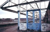 The derelict Manors North in the 1980s looking south east along platform 1 with 2-5 off to the left. The ECML platforms 6-9 of Manors East run across the picture in the background (accessed via the white footbridge) and the spire of Newcastle's All Saints Church is visible on the far right through the shell of the building. No trace remains of Manors north station but the 2 surviving platforms at Manors East are currently (2013) served by Northern trains on the Morpeth - Metro Centre route. <br><br>[Ian Dinmore&nbsp;//]