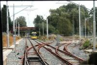 The junction at St Werburgh's Rd, where the new Metrolink line to Manchester Airport diverges, was complete in 2013 although not yet connected to tracks on the branch itself. View from behind the driver of a tram taking the recently reopened <I>Midland Main Line</I> to East Didsbury. <br><br>[Mark Bartlett&nbsp;31/07/2013]