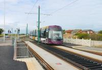 The quality of finish on the new Blackpool and Fleetwood tram stops is a complete contrast to the old system. <I>Flexity</I> 013 slows for the Rossall School stop on a service from Fleetwood. [See image 32523] for the same location in 2011 (and earlier).  <br><br>[Mark Bartlett&nbsp;10/08/2013]