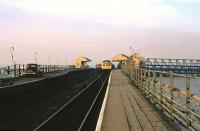 Cars on New Holland Pier in 1975 queueing for the ferry, while a DMU for Cleethorpes waits in the background to connect with the next arrival from Hull. [See image 42310]<br><br>[Ian Dinmore&nbsp;//1975]