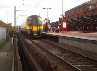 The unusual sight of a passenger train on platform 6 in Rugby (a 350 destined for Euston). As the station is run by Virgin Trains, there is a gent in a red shirt helping London Midland passengers. The path on the left leads from the station underpass to a multi-storey car park.<br><br>[Ken Strachan&nbsp;30/08/2013]