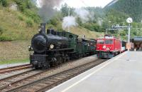 <I>Swiss Fellsman?</I> Rhaetian Railways operate the metre gauge network in south east Switzerland. It is mainly electric but they have some diesels and also preserved steam on their books. RhB electric 605 <I>Silvretta</I>, a mere 60 years old, has just run round the Davos portion of the <I>Glacier Express</I> at the junction at Filisur but is held briefly while RhB 108 <I>Engiadana</I>, a splendid looking 2-8-0 dating from 1906, departs for Chur with a well loaded special excursion. 108 and sister 107 were retained for snowplough duties long after 27 other class members were sold to Siam and Brazil.<br><br>[Mark Bartlett&nbsp;14/09/2013]