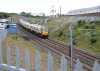 The 14.11 Helensburgh Central - Edinburgh Waverley slows for the Armadale stop on 23 September 2013, passing another new housing development. <br><br>[John Furnevel 23/09/2013]