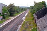 The fire damaged station building at Crookston looking west in 1990 as the line to Paisley Canal is prepared for re-opening. A stack of lifted track stands in the distance.<br><br>[Ewan Crawford //1990]