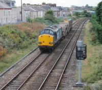 DRS 20303 and 37605 pass the site of Morecambe Euston Rd, the town's LNWR station, as they slow to a stop prior to reversing. 37605 will then head down the Heysham branch with two empty flasks for the nuclear power stations. <br><br>[Mark Bartlett&nbsp;26/09/2013]