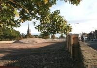 The station site at Dalkeith, now cleared and ready for construction of the new supermarket. View east towards the town centre on 5 October 2013. The A6094 Eskbank Road is on the right and the 167 ft spire of the former West Church on Old Edinburgh Road stands in the left background. [See image 37347] <br><br>[John Furnevel&nbsp;05/10/2013]