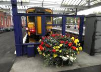The 10.27 service to Glasgow Central stands in the bay at Kilmarnock station on 16 October behind another of the colourful planters maintained by the local Hurlford Gardening Club.<br><br>[John Yellowlees&nbsp;16/10/2013]