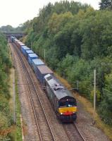 DRS 66427 heads a southbound container train past the site of Boar's Head Junction on 2 October 2013. The junction was to the right of the locomotive and ran via Red Rock to join the Preston - Bolton line at Adlington. The line was lifted in the early 1970s.<br><br>[John McIntyre&nbsp;02/10/2013]