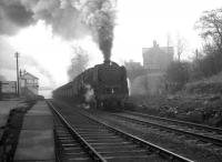 A trainload of iron ore on its way from Tyne Dock to Consett photographed passing through Beamish station on a February morning in 1964. Hard working 9F 2-10-0 no 92097 heads the procession, while bringing up the rear is WD 2-8-0 no 90434, having joined the train at South Pelaw. <br><br>[K A Gray&nbsp;15/02/1964]