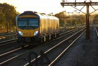 Heading west into the setting sun on 9 October 2013, a TransPennine service from Cleethorpes to Manchester Airport leaves Barnetby, with the array of semaphore signals standing guard over the approach to Wrawby Junction.<br><br>[John McIntyre 09/10/2013]