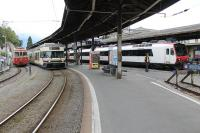 Vevey, on the shore of Lake Geneva, is a meeting point for metre and standard gauge networks. Here an articulated unit on a Blonay service waits to leave the narrow gauge platform with an older single car stabled alongside. On the right a SBB EMU waits in a standard gauge bay.<br><br>[Mark Bartlett&nbsp;10/09/2013]