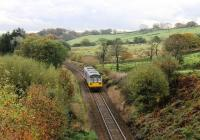 Coasting downhill through Lancashire moorland scenery in October 2013, a Northern Pacer approaches the level crossing and closed station at Turton & Edgeworth. 142036 is on a Blackburn to Manchester Victoria service. This line, singled in the 1970s, was redoubled around Darwen in 2015 for the planned circular services to Burnley using the reinstated Todmorden chord. <br><br>[Mark Bartlett&nbsp;26/10/2013]