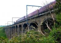 An up EWS coal train crossing the viaduct over the River Aln, just north of Alnmouth station, in May 2004. The listed structure (also referred to as Lesbury Viaduct) was built by Robert Stephenson in 1848/9.<br><br>[John Furnevel 24/05/2004]