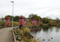 Just beyond the end of Acccington's Bury line platforms the 1:37 Baxenden bank started on a bridge over a mill reservoir. The trackbed greenway now runs between the columns of that demolished bridge as a feature of what is now this urban park. <br><br>[Mark Bartlett&nbsp;15/11/2013]