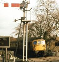 A fine spring Saturday morning in April 1985 sees a class 33 with an Exeter - Barnstaple train draw slowly into Eggesford station over the level crossing.<br><br>[John Stanford&nbsp;/04/1985]