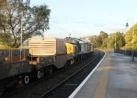 The morning Crewe to Sellafield flasks rumble through Grange-over-Sands station behind DRS EE Type 3s 37608 and 37682 on 17 October 2013.<br><br>[Mark Bartlett&nbsp;17/10/2013]