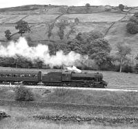 Just over two years after its acquisition by the Keighley and Worth Valley Railway, ex Swedish State Railways WD 2-8-0 No. 1931 heads an afternoon train up the valley between Haworth and Oxenhope, thought to be on a Sunday in July 1975. Since then the loco has acquired a four axle tender and now runs with the fictitious identity of BR No. 90733. <br><br>[Bill Jamieson&nbsp;/07/1975]