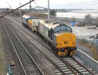 Diverging onto the Bare Lane chord at Hest Bank on 18 December is this trip working to Heysham Power Station from Sellafield. DRS 37688 brings up the rear of the train conveying a single flask led by 37606. The train will reverse at Morecambe to access the Heysham branch. <br><br>[Mark Bartlett&nbsp;18/12/2013]