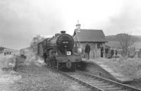 42737 at Broughton on 29 March 1964 with <I>Scottish Rambler no 3</I>. The <I>Crab</I> had brought the special from Symington to what was then the limit of the former route to Peebles (the line east having closed in 1954). This surviving section had been retained to serve a nearby meat processing facility. On the left is the old island platform built in 1896 to serve the Talla Railway [see image 6635]. <br><br>[John Robin&nbsp;29/03/1964]