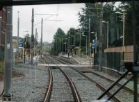Metrolink driver's view from a Manchester bound tram entering Derker station. The original wooden platforms, from when the station opened to replace Royton Junction in 1985, were replaced when Metrolink rebuilt the line after the 2009 closure. [See image 21153] for a <I>heavy rail</I> view of this location. <br><br>[Mark Bartlett&nbsp;31/07/2013]