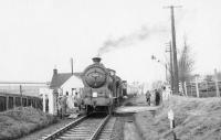 The SLS <I>'Farewell to Peebles'</I> railtour on the level crossing at Pomathorn on 3 February 1962. The special is hauled by J37 0-6-0 no 64587 [see image 28603]. The large building in the left background is Pomathorn paper mill, which closed in 1975.<br><br>[David Stewart&nbsp;03/02/1962]