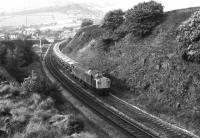 A lengthy train of <I>Presflo</I> hoppers takes the Hope Valley line at Chinley North Junction in the summer of 1979. Motive power on this eastbound service is one of the split headcode Class 40s.<br><br>[Mark Bartlett&nbsp;//1979]