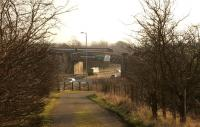 A class 156 DMU crosses the <I>Cutty Sark</I> bridge over the A8 on its way to Baillieston, during the morning of 30th January 2014. This viewpoint on Bredisholm Road will disappear during the planned Baillieston - Newhouse M8 extension works. [See image 46140]<br><br>[Colin McDonald&nbsp;30/01/2014]