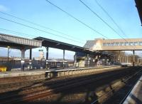 The new down side footbridge steps are sited approximately on the throat for the line into the former bay platforms at Wakefield Westgate. The view shows the north end of the original brick platform wall and the long concrete extension to beyond the new footbridge, together with a more recent short extension beyond. The roofline and clock tower seen through the canopy are located within the walls of the maximum security HM Prison Wakefield along the other side of Love Lane from the northern end of the station. <br><br>[David Pesterfield&nbsp;04/02/2014]