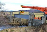 The first girder is slowly eased into position at Dulnain Bridge on the Strathspey Railway on 14 February 2014.<br><br>[John Gray&nbsp;14/02/2014]