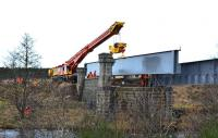 View south across the River Dulnain towards Broomhill station on 14 February 2014 as the Colas Crane approaches the bridge with the second girder. <br><br>[John Gray&nbsp;14/02/2014]