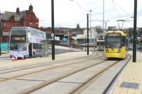 A 4-car Metrolink tram leaves the old railway formation at Oldham Mumps and climbs to the interchange stop, one of four new Metrolink boarding points through the town centre.  A large railway bridge once dominated the background here and the location, including the surviving building on the left, featured in a Railscot mystery image which ran in March 2012 [see image 37965]<br><br>[Mark Bartlett&nbsp;13/02/2014]