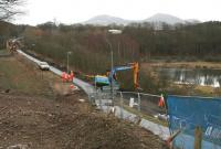 View south along the now closed <I>Black Path</I> towards the <I>Red Bridge</I> linking Galashiels and Tweedbank on 26 February. The JCB is standing at the point where the path and the old Waverley trackbed split, with the former climbing to join Winston Road (from which the photograph was taken) and the latter continuing north under the road towards Galashiels station [see image 46466].<br><br>[John Furnevel&nbsp;26/02/2014]