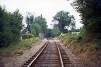 A view along the former Harpenden - Hemel Hempstead line on 7th August 1976. The location is Sunnyside, a minor crossing to the east of Beaumont's Halt. The battered fixed signal is protecting the level crossing at the halt. The line remained in use for occasional ash traffic until 1979.<br><br>[Mark Dufton&nbsp;07/08/1976]