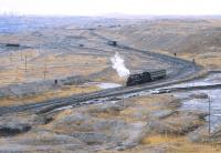 View over part of the enormous Jalainur Opencast Coal Mine, Inner Mongolia, with its own fleet of SY 2-8-2s, one of which is seen here in April 2000 with a local staff works train.<br><br>[Peter Todd&nbsp;21/04/2000]