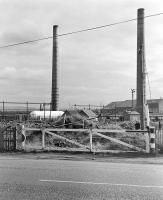 Looking north over the former level crossing that once took the NCB line to Woolmet Colliery (closed in 1966) over the A6095, photographed in the early 1980s [see image 46571].  The chimneys of Niddrie Brickworks dominate the scene. The whole area is now a shopping mall.<br><br>[Bill Roberton&nbsp;//]
