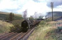 Britannia Pacific no 70003 <I>John Bunyan</I> northbound on Beattock approaching the summit distant signal on the last day of July 1965. The exhaust beyond the road bridge in the background is from banker 80045 bringing up the rear of the train.   <br><br>[John Robin 31/07/1965]
