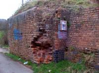 Here is an abutment that is so decayed, it is positively artistic. It stands (just) adjacent to a farm road in the Ansley Common area of Nuneaton. Even the notice about trapping dogs (?) has been vandalized.<br><br>[Ken Strachan&nbsp;21/03/2014]
