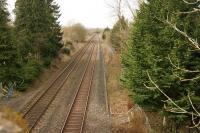 There was not much to see as far as the former Adlestrop station was concerned when it was visited on 4 March 2014. The degraded remains of the platforms were just visible and the station house still stood as a private residence through the trees on the left. [Ref query 3485]. Photographed from the bridge carrying the A436 over the railway.<br><br>[John McIntyre&nbsp;04/03/2014]