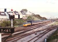 A Westbound BR <I>InterCity 125</I> HST - most likely bound for Cardiff or Swansea - passes the branch to Uskmouth and the semaphore signals for East Usk yard in September 1988. Llanwern steelworks (proposed 1862, built 1962) is in the background.<br><br>[Ken Strachan&nbsp;/09/1988]