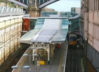 The view east from Waverley Bridge showing the new canopy over the 'sub' platforms. The metal/glass structure is echoed in the refurbished Market Street station entrance as well as the Edinburgh Council HQ in the background. Hiding in the shadows alongside platform 8 is the 12.07 service to Milngavie. [See image 17536]<br><br>[John Furnevel&nbsp;11/04/2014]