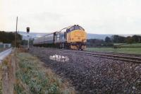 The heady days of loco-hauled trains along the Welsh Marches came to a halt in the late eighties. A southbound large logo class 37 passes the site of Ponthir station in September 1988, some 26 years after closure. The upper reaches of the town of Cwmbran  can be seen in the right background. [Ref query 5624]<br> <br><br>[Ken Strachan&nbsp;/09/1988]