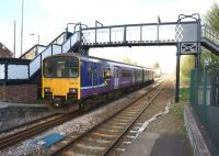 A view east from the platform at Rainhill on 19 April 2014 with a Manchester bound service passing under the footbridge. Rainhill signal box can be seen beyond the train.<br><br>[John McIntyre&nbsp;19/04/2014]