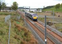 Shortly after passing through Caldercruix and skirting Hillend reservoir, 334013 is about to run past the remains of the demolished Forrestfield station. The train is the 11.27 Milngavie - Edinburgh, which runs non-stop between Drumgelloch and Bathgate. The cyclists on the right are using the cycle path/walkway built to replace that reclaimed by the reopened railway. [See image 9671]<br><br>[John Furnevel&nbsp;08/05/2014]